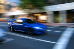 Speeding blue car. Blue car speeding through the city Stock Photography