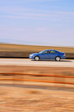Speeding Blue Car with Blurred Background. A blue car speeds by with intentional blurred background Stock Photo