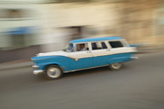 A speeding blue and white 1955 Ford station wagon driving through the streets of Havana, Cuba Royalty Free Stock Photo