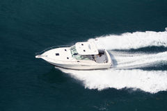 Speeding Boat. Speeding fishing yacht on blue water causing lots of waves Royalty Free Stock Image