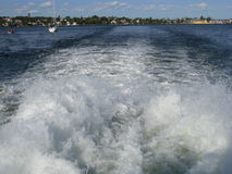 Speeding boat wake on sea. The white foamy wake of a speeding boat. View from rear of boat.  Trail of wake leads to the distance.  Sailboats in the background Royalty Free Stock Photos