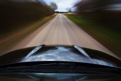 Speeding car. Fast moving Mercedes Benz C63 AMG, driving down a country road with motion blur Stock Photography