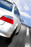 Car speeding. White car speeding on the highway under a beautiful cloudy sky Stock Photo