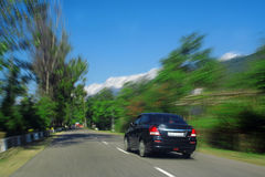 Speeding Car Blur snowpeaked himalaya road India. A Speeding car  racing through a blurred Tree lined Rural Route Highway in kangra valley area with  a backdrop Stock Photos