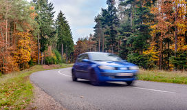 Speeding car blurred arred road through colorful autumn trees Royalty Free Stock Photo