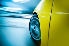 Speeding Car. At Night. Long Exposure City Drive. Front Wheel in Motion Closeup. Motion Blur Transportation Concept Royalty Free Stock Image