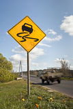 Speeding car passing slippery road sign Stock Images