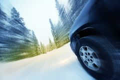 Speeding Car in Winter. Speeding Car on Countryside Winter Road. Road Covered by Heavy Snow. Motion Blur Stock Photography