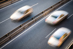 Speeding cars. Cars running on road in two directions Royalty Free Stock Photography