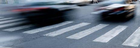 Speeding cars. Urban scene of cars running on pedestrian crossing Stock Images