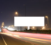 Speeding cars on modern Road infrastructure with blank hoarding for text messages, artistic long exposure shot Royalty Free Stock Images