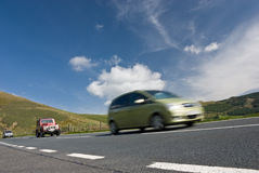 Speeding cars on mountain road. Wales, UK Royalty Free Stock Photography