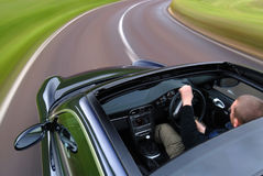 Speeding curve. A man speeding in a black car on the curve of a road Stock Images