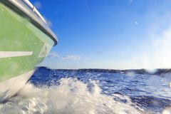 Speeding fishing motor boat with drops of water. Blue ocean sea water wave reflections with fast fishing yacht. Motor boat in the. Blue ocean. Ocean yacht stock image