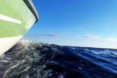 Speeding fishing motor boat with drops of water. Blue ocean sea water wave reflections with fast fishing yacht. Motor boat in the. Blue ocean. Ocean yacht stock images