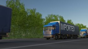 Speeding freight semi truck with IMPORTED caption on the trailer. Road cargo transportation. Seamless loop 4K clip stock video footage
