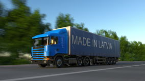 Speeding freight semi truck with MADE IN LATVIA caption on the trailer. Road cargo transportation. 3D rendering Stock Image