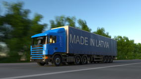 Speeding freight semi truck with MADE IN LATVIA caption on the trailer. Road cargo transportation. Seamless loop 4K clip. Speeding freight semi truck with MADE stock video