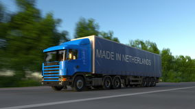 Speeding freight semi truck with MADE IN NETHERLANDS caption on the trailer. Road cargo transportation. 3D rendering Royalty Free Stock Photography