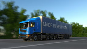 Speeding freight semi truck with MADE IN NEW YORK caption on the trailer. Road cargo transportation. Seamless loop 4K stock footage