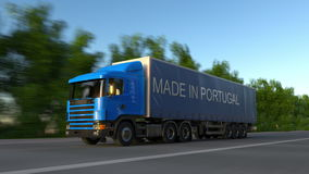 Speeding freight semi truck with MADE IN PORTUGAL caption on the trailer. Road cargo transportation. Seamless loop 4K. Animation stock video footage