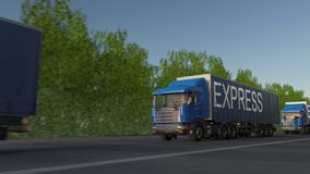 Speeding freight semi trucks with EXPRESS caption on the trailer. Road cargo transportation. Seamless loop 4K clip stock video