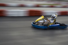 Speeding Go Kart. A young boy in a go kart goes speeding around a race track Royalty Free Stock Photo