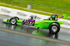 Speeding green dragster on a drag strip Stock Photography