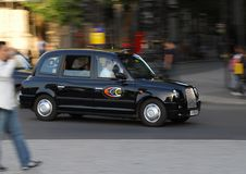 Speeding London black cab. London, United Kingdom - September 11 2007: A london black Cab taxi speeds past pedestrians stock photo
