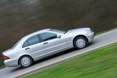 Speeding luxury car panned. Speeding car shot on the mountain road. Panning technique was used to emphasize the movement Royalty Free Stock Images