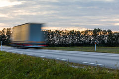 Speeding motion blur oncoming trucks with glowing lights on the stock photography