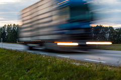 Speeding motion blur oncoming trucks with glowing lights on the stock photo