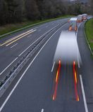 Speeding motion blur trucks with glowing lights on the highway royalty free stock image