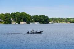 Speeding motor boat and boathouses Stock Image