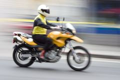 Speeding Motorcycle 1. A speeding motorcycle with intentional camera motion blur royalty free stock image