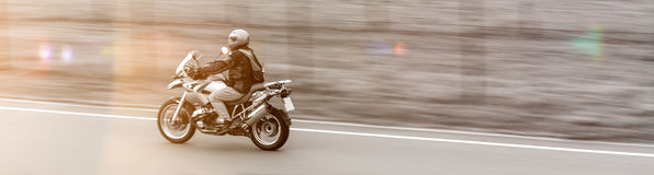 Speeding motorcycle  panoramic view sun color Royalty Free Stock Photo
