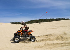 Speeding quad in sand dunes Royalty Free Stock Photos