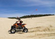 Speeding quad in sand dunes. Male riding ATV quadbike in the sand dunes speeding past the camera Royalty Free Stock Photos