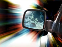 Speeding Race Car Mirror Traveling. A car is speeding on a road and there are red, yellow and blue zooming lines with movement. There is a rear view mirror with Stock Photo