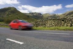Speeding red car, Lake District National Park. Speeding red car, Road A592,  Lake District National Park, UK Stock Image