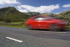 Speeding red car, Lake District National Park. Speeding red car, Road A592,  Lake District National Park, UK Royalty Free Stock Image