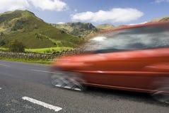 Speeding red car, Lake District, UK. Speeding red car, Road A592,  Lake District National Park, UK Stock Image