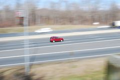 Speeding red car rushing down highway stock photos