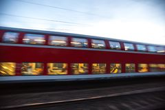 Speeding red passenger train in the evening royalty free stock photo