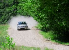 Speeding on rural road. Silver car at high speed on a country-side road without pavement Stock Image