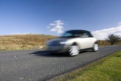 Speeding silver car. Dartmoor, UK Royalty Free Stock Photography