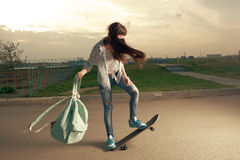 Speeding skateboarding woman at city with backpack Royalty Free Stock Photo