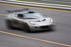 Speeding Sports Car. A fast silver sports car speeding down the road. Slight motion blur stock photo