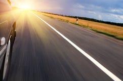 Speeding Towards Sun. Car on a highway speeding towards the sun Stock Image