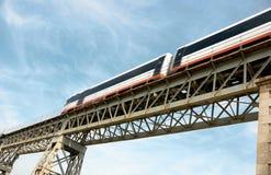 Speeding train. Train speeding across an old iron brigde Stock Image